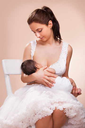mom breastfeeding in white dress