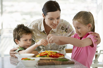 mom helping kids prepare meal in kitchen