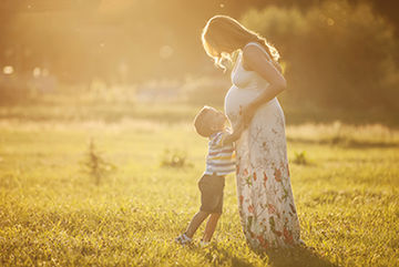 son kisses pregnant mom's belly in field at sunset