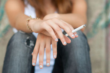 Closeup of teenage girl holding cigarette