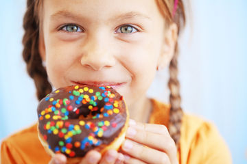 Young girl eating chocolate donut