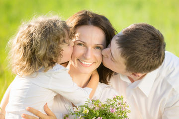 Two boys kissing mom