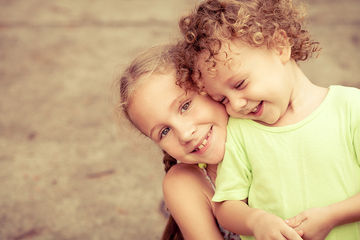 Two smiling young siblings