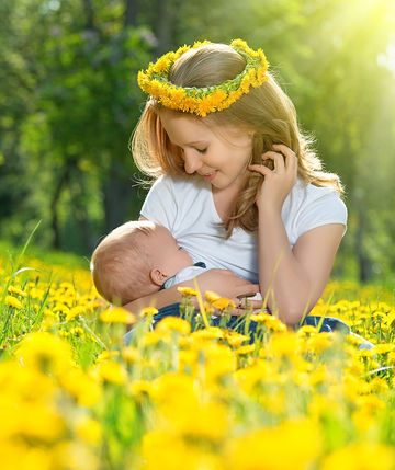 mother breastfeeding her baby in nature wearing flower crown