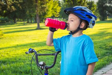 Boy in Helmet Drinking from a Bottle