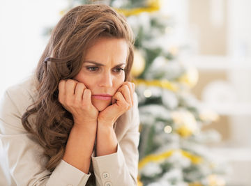 Upset Woman Sitting in Front pf Christmas Tree