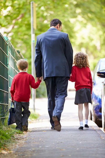 Father in suit walking kids to school