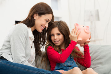 Mother with daughter holding piggy bank