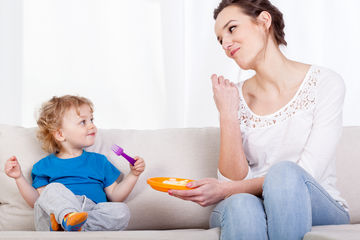 Mom and Toddler Eating on Couch