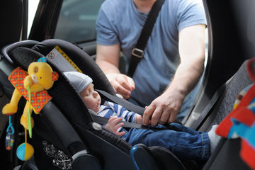 Dad Putting Baby in Car Seat Shutterstock