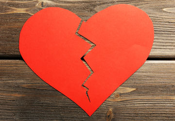 Broken red paper heart on wood background