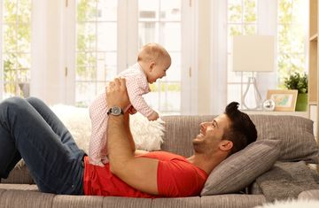 Father holding baby on couch