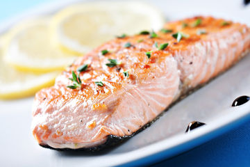 Cooked salmon on plate with lemon slices
