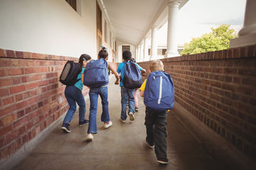 Four children walking through outdoor hallway