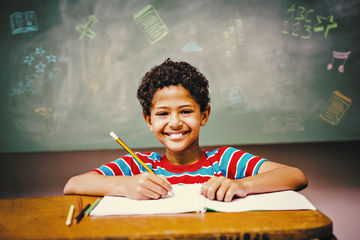 Boy Writing in Notebook with Chalkboard Behind Him