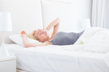 Woman in bed covering face