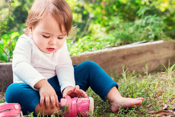 Toddler girl putting on shoe