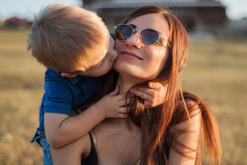 toddler kissing mom in sunglasses