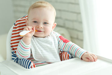 Happy Baby Eating Spoon In High Chair
