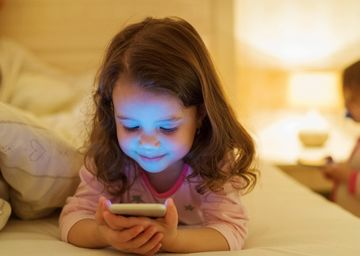 Kid With Phone in Bed