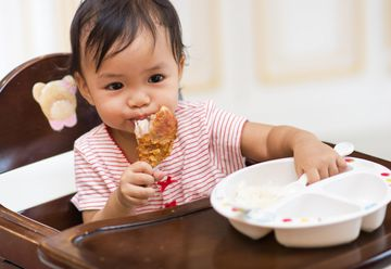 Asian Toddler Eating Chicken Meat