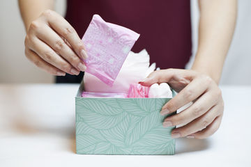 Woman Holding Pad From Box Of Feminine Supplies