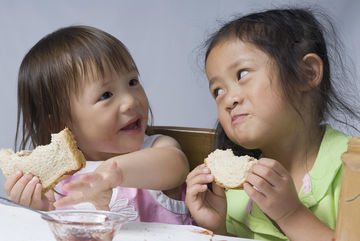 sisters eating peanut butter and jelly sandwiches