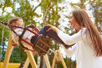 mom pushing child on swing at playground