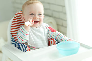 smiling baby boy in high chair