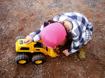 toddler in pink hat playing with truck