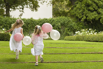 two flower girls running with balloons