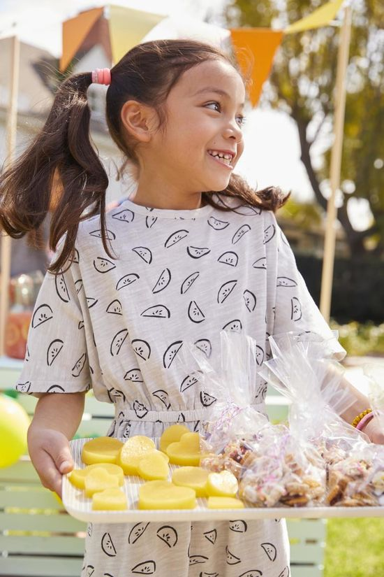 Young Girl Holding Tray of Treats Lemonade Stand