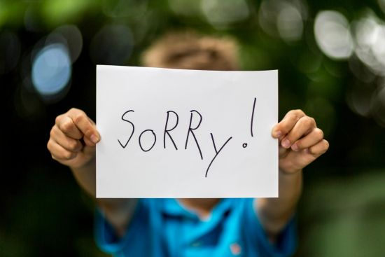 boy holding sign that says sorry