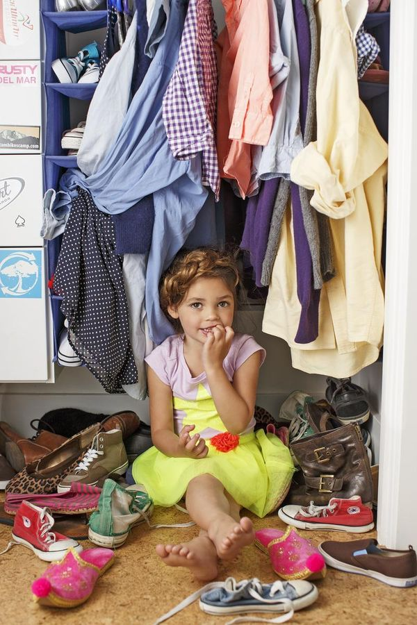 Girl with Curly Hair Sitting in Closet