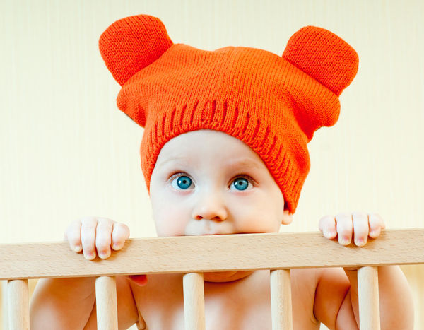 baby in crib wearing orange hat