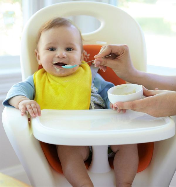 Baby Eating Infant Cereal In High Chair