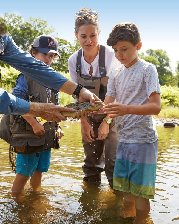 Family Holding Fish Caught From Fly Fishing