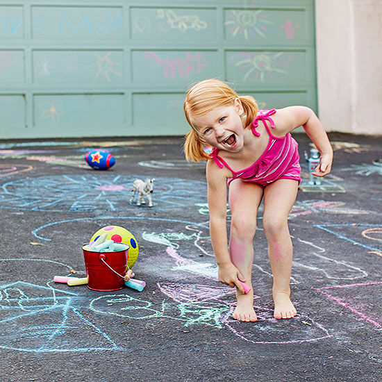 child playing with chalk in driveway