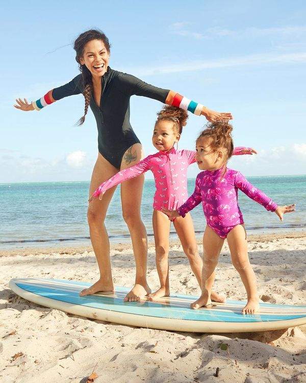 Laura Scott and Daughters Stand on Surfboard RV Trip