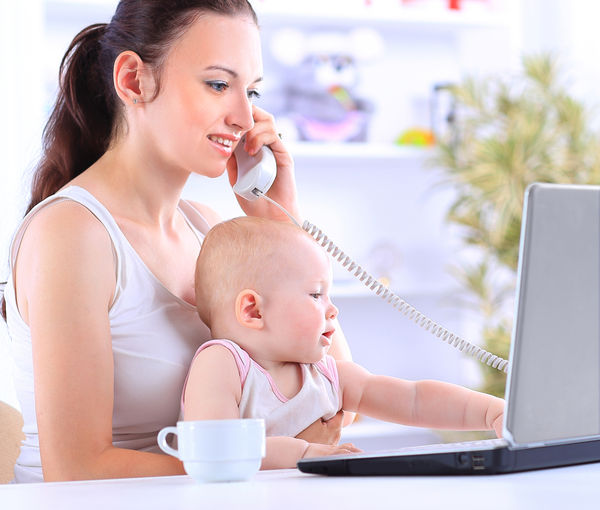 Mom working on computer with baby on lap