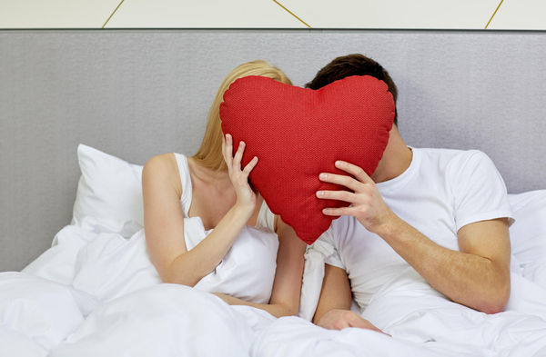 Couple in Bed With Heart-Shaped Pillow